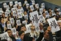 "Medical professionals hold up protest signs to indicate they are at ""breaking point"", during a meeting between public sector doctors, the government and the Hospital Authority at Queen Elizabeth Hospital in Kowloon, on January 26. Photo: Felix Wong"
