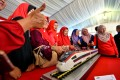 People pose with a model train for the East Coast Rail Link project. Photo: Xinhua