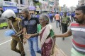 An elderly woman is helped near St Anthony's Shrine after a blast in Colombo, Sri Lanka. Photo: AP