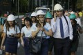 Wearing helmets, employees evacuate their building after an earthquake near Manila on Monday. Photo: AP