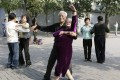 Elderly people dance during a morning exercise session at the Temple of Heaven park in Beijing. Photo: Reuters