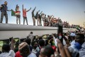 Sudanese protesters from the city of Atbara, flash the V-sign for victory and wave national flags atop a train, as it arrives at the Bahari station in Khartoum. Photo: AFP