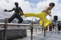 Mainland actor Mei Zhiyong, dressed as the late Hong Kong kung fu star Bruce Lee, performs in front of Lee's statue at the Avenue of Stars in Tsim Sha Tsui. Photo: Edward Wong