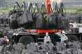 Workers move waste containing radiated soil, leaves and debris from the decontamination operation at a storage site in Naraha town. Photo: Reuters