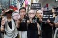 Pro-democracy activists hold masks with faces of jailed Occupy leaders during a march against proposed changes to the extradition law, in Hong Kong on April 28. Photo: EPA-EFE