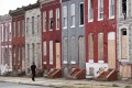 Pedestrians pass by a row of boarded up houses in Baltimore. Photo: AFP