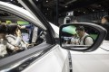 Attendees look at an electric sport utility vehicle on display at last month's Auto Shanghai 2019 show in China. Photo: Bloomberg