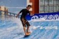 A member flowboards at Wavorhouse Urban Surf Club in Beijing. The indoor sport is a combination of various board sports. A surf simulator developed in China by the club's founder produces waves three metres high.