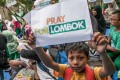 "A child holds up a placard that reads ""pray for Lombok"" following the earthquake in August 2018. Photo: AFP"
