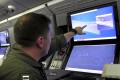 US Navy personnel point at a computer screen showing Chinese activity on the Fiery Cross Reef in the Spratly Islands in the South China Sea. An Australian scholar said Chinese ships pointed lasers at them during a flight over the disputed sea. Photo: Reuters