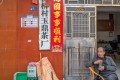 Cui Dongliang, at his tea shop in Yangqiao, Zhejiang province, in China. Next to the door is a sign that indicates his social credit score, which he himself upgraded to five stars using stickers. Photo: Gilles Sabrié for The Daily Telegraph Magazine
