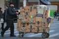 A delivery person pushes a cart full of Amazon boxes in New York on February 14, 2019. Photo: Reuters