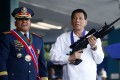 Philippine President Rodrigo Duterte, right, holds an Israeli-made Galil rifle presented to him by former police chief Ronald Dela Rosa. Photo: AP