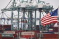 Chinese shipping containers are stored beside a US flag after they were unloaded at the Port of Los Angeles in Long Beach, California. Photo: AFP