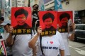 Protesters cover their faces with posters of Chief Executive Carrie Lam during the march from Causeway Bay to the government headquarters in Admiralty. Photo: Winson Wong
