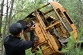 A visitor takes a picture of the wreckage of a bus in the ghost city of Pripyat during a tour in the Chernobyl exclusion zone. Photo: AFP