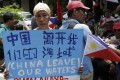 A protester outside the Chinese consulate in Manila calls for China to leave Philippine waters. Photo: AP