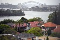 Property analysts point to the results of a land auction on June 8 where 62 per cent of properties were sold as an indicator that the property market was turning around. Single detached houses in inner Sydney, Australia are framed by the Sydney Harbour Bridge. Photo: EPA