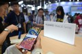 People look at new Huawei smartphones during the CES Asia 2019 trade show in Shanghai on June 11, 2019. Photo: Agence France-Presse
