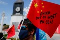 A Filipino activist holds a paper Chinese national flag during a protest in Manila against the sinking of the fishing boat. Photo: EPA