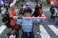 A police officer stops traffic as demonstrators protest at the G20 summit in Osaka. Photo: Bloomberg