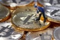 A small toy figure is seen on representations of the Bitcoin virtual currency in this illustration picture on December 26, 2017. Photo: Reuters