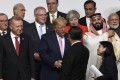 US President Donald Trump (centre) shakes hands with his Chinese counterpart Xi Jinping before a group photo at the G20 summit in Osaka on Friday. Photo: AP