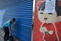 An Indonesian worker cleans the door of a market closed due to protests over the Indonesian election result. Photo: AFP