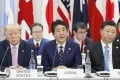 Japanese Prime Minister Shinzo Abe (centre) speaks at the G20 summit in Osaka on Friday, flanked by US President Donald Trump and Chinese leader Xi Jinping. Photo: Kyodo