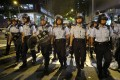Police officers in anti-riot gear patrol outside the headquarters of the force in Wan Chai, early on June 22. Protesters laid siege to the building for 15 hours the previous day. Photo: Edmond So