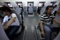 People learn basic driving skills on simulators in Beijing, China. Photo: AP