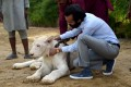 Bilal Mansoor Khawaja, a private zoo owner, sits with his white lion in Karachi. Photo: AFP