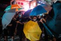 Masked demonstrators holding umbrellas stand off against riot police on Nathan Road, in the Mong Kok tourist district of Hong Kong on July 7. Photo: Bloomberg