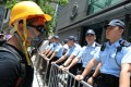 A protester in makeshift safety gear stands off with officers at the police headquarters, in Wan Chai on June 21. Photo: Dickson Lee