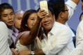 A supporter takes a selfie with Philippine President Rodrigo Duterte. Internet speeds in the country lag the region's. Photo: AFP