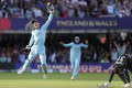 England's Jos Buttler celebrates after running out New Zealand's Martin Guptill, right, with the last ball of the last over of the Cricket World Cup final. Photo: AP