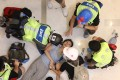 An injured woman is treated at a shopping mall in Sha Tin on Sunday during clashes between extradition bill protesters and police. Photo: EPA
