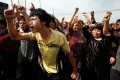 An angry crowd clashes with Chinese paramilitary police in Xinjiang. Photo: Reuters
