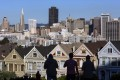 Pedestrians stand in front of Victorian homes and the downtown skyline in San Francisco, California. Chinese investment in US homes fell in the past year. Photo: Bloomberg