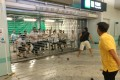 A mob of men in white T-shirts try to force open shutters at Yuen Long station. Photo: Handout