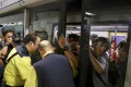 Protesters prevent the doors of a train closing as MTR staff try to stop them at Admiralty station. Photo: Nora Tam