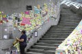 "A staff member of the Legislative Council complex in Admiralty removes sticky notes from a ""Lennon Wall"" set up along a staircase leading to government offices, on July 22. The colourful collages have sprung up across the city in support of those protesting against the government. Photo: Nora Tam"