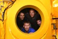 French biologist, marine naturalist and photographer, Laurent Ballesta (bottom poses inside his diving chamber with his crew in Marseille. Photo: AFP