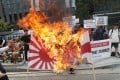 South Korean college students burn a banner showing an image of a Japanese rising sun flag and Japanese Prime Minister Shinzo Abe. Photo: AP