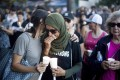 Mourners comfort one another on July 29 during a vigil for victims of the Gilroy Garlic Festival shooting. Photo: AP