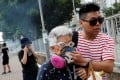 An elderly woman is helped by a demonstrator after police fire tear gas during a protest in Tin Shui Wai on August 5. Photo: Reuters