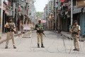 Indian security personnel stand guard on a deserted street in Jammu on Monday. Photo: Reuters