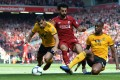 Liverpool's Mohamed Salah (C) in action against Jonny (L) and Willy Boly (R) of Wolverhampton Wanderers in the English Premier League. Photo: EPA