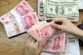 China's central bank set the midpoint exchange rate at 7.0211 on Monday, the third consecutive trading day that Beijing has set a rate weaker than 7 to the US dollar. Photo: AFP