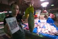 Fish Vendor Wu Weibin at a wet market in Shenzhen, China, takes mobile payment. Photo: SCMP